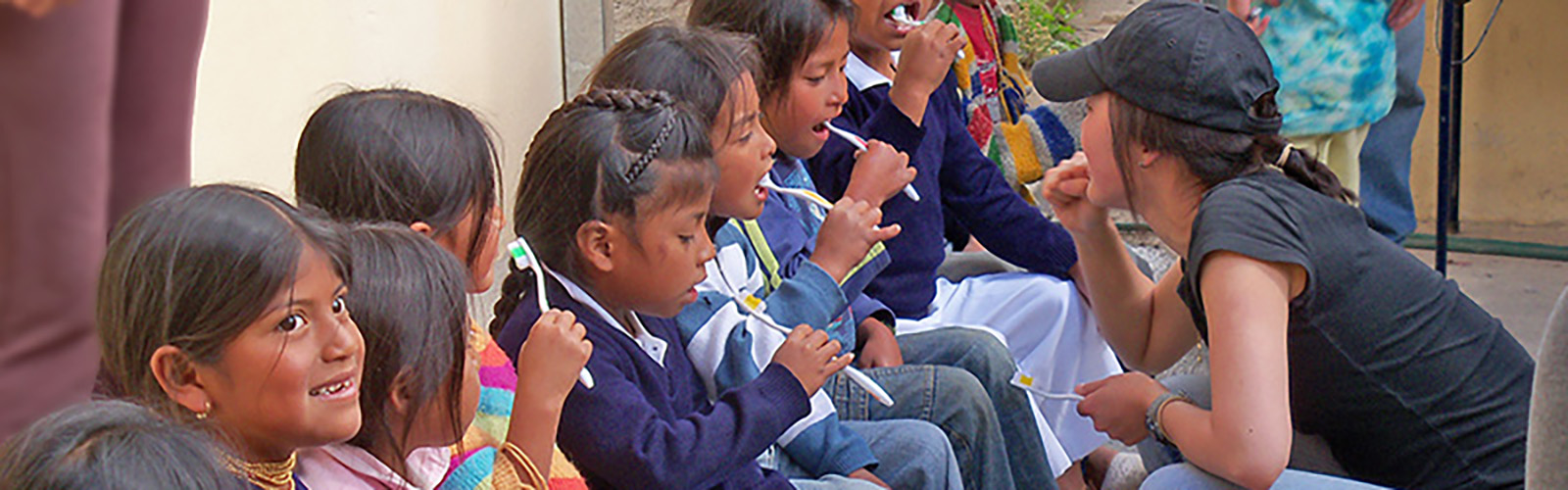 Ecuador children are learning to brush their teeth while sitting in a row, with a UW woman student in front of them showing them how.