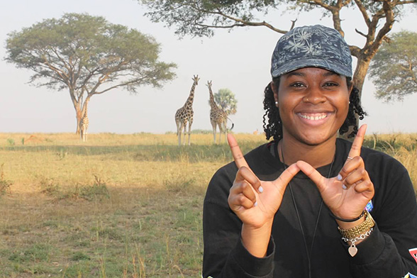 A student makes the W sign with her hands, standing in front of an African savannah with two giraffes in the background.