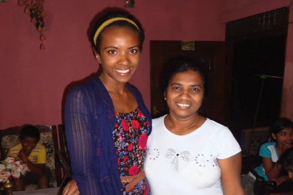 A student stands with her arm around a Sri Lankan woman.